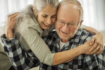 Affectionate elderly couple share a spontaneous hug.