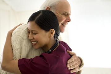 Smiling female nurse hugging an elderly male patient.