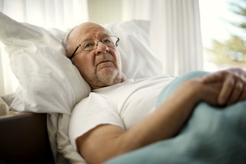 Concerned senior man lying in bed with his hands clasped.