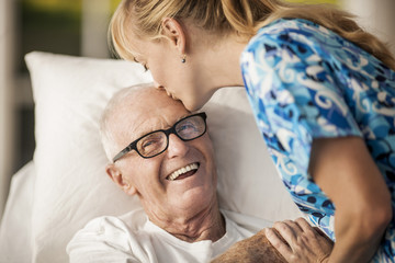 Friendly young rest home nurse cheers up her elderly male patient with a kiss on his forehead.