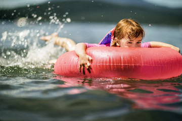 Young girl splashing in a lake on an inflatable tube.