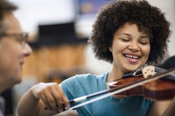Teenage girl learning to play violin.