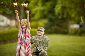 Young girl dancing with sparklers in the back yard with her father.