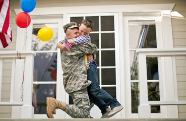 Happy army soldier hugging his young son on the porch of their home.