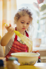 Little blonde girl kneading dough in kitchen