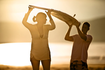 Couple carrying a surfboard on the beach.