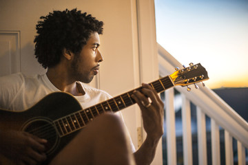 Pensive young man playing an acoustic guitar.