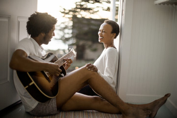 Young man playing guitar for his smiling partner.