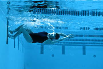 Female swimmer pushing off from the swimming pool wall.