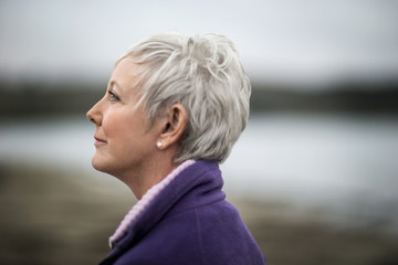 Portrait of a mature woman enjoying the view at the beach in winter.
