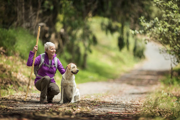 Portrait of a cheerful mature woman taking a break from hiking in the forest to pet her dog.