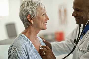 Cheerful mature woman gets her heartbeat checked by a friendly doctor.