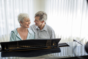 Affectionate mature couple enjoy playing the piano together.