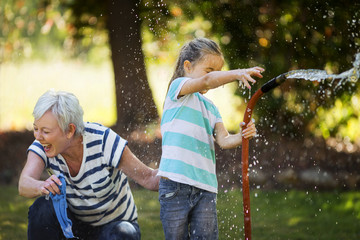 Happy grandmother and granddaughter spraying a hose on a summer day.