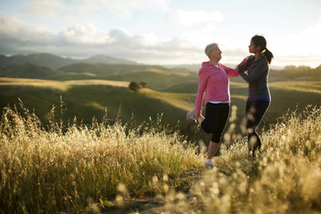 Young woman helping a senior woman to stretch while exercising in a rural landscape.