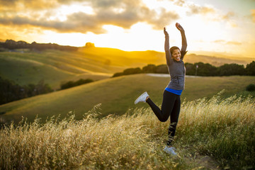 Smiling young woman jumps for joy in the countryside at sunset.