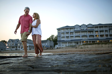 Mature couple holding hands and smiling as they walk barefoot on the beach at sunset.