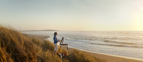 Content mature woman painting a beach scene at sunset.