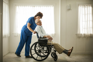 Laughing senior man being pushed in his wheelchair by a female nurse.