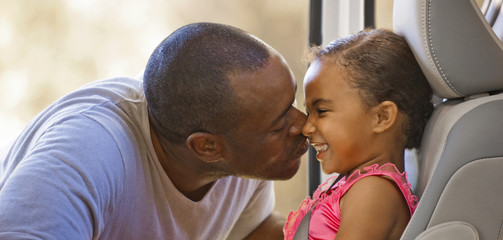 Mid adult man kissing his young daughter on the nose.