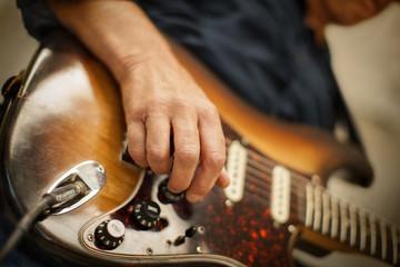 Mature adult man playing an electric guitar.