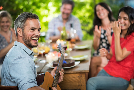 Summertime, man playing guitar for his friends on a terrace