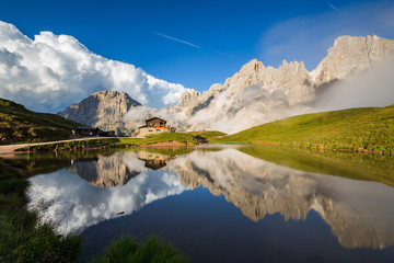 Fototapete - The Pale di San Martino peaks (Italian Dolomites) reflected in the water, with an alpine chalet on background.