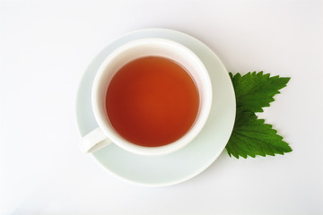 Cup of tea and leaf of mint isolated on white background