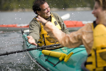 Happy mid-adult couple sitting in a kayak on a lake.