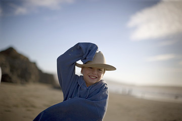 Smiling young boy wearing a hat on the beach.