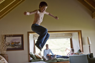 Young boy jumping on a bed.