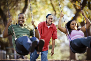 Young adult man pushing two friends on a swing while outside.