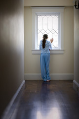 Teenage girl in pyjamas looking out a window.