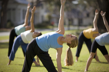 Mid-adult woman practicing yoga with a group of women outside.