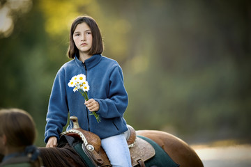 Girl holding flowers while on horseback.