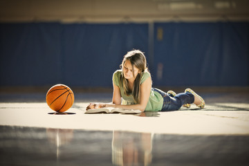 Teenage girl reading on the floor of a basketball gym.