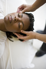 Young woman receiving a head massage with her eyes closed.