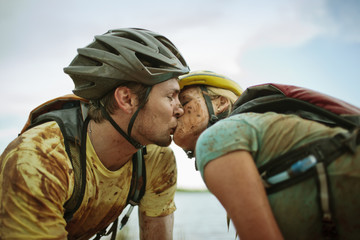 Muddy young couple share a kiss while taking a break from mountain biking by a lake.
