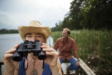 Mature woman takes a break from looking through the binoculars while bird watching at the lake.