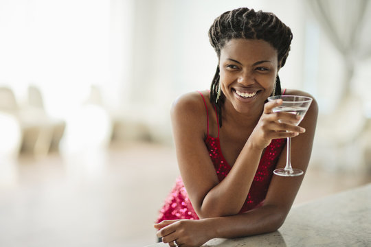 Smiling young woman enjoying a cocktail at a bar.