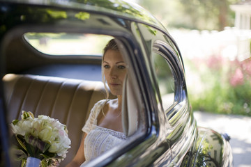 Young adult bride holding flowers in a car on her wedding day.
