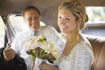 A bride sitting in a car holding a bouquet