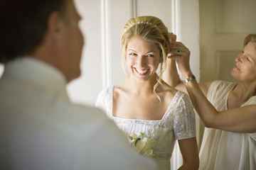A bride has her hair pinned up by her mother