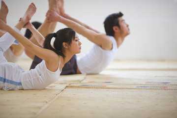 Young man and young woman practicing yoga.