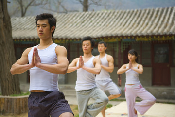 Group of young adults practicing yoga together outdoors.