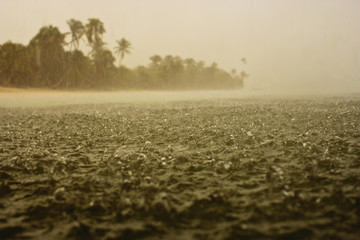 Hard rain splashing on the surface of the sea near a tropical island.