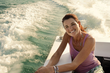 Portrait of smiling mid adult woman riding in the back of a boat in the sunshine.