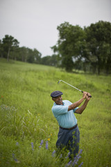 Mature man swinging a golf club in tall green grass.