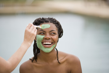 Young woman with bare shoulders smiling while having a mud face mask applied.