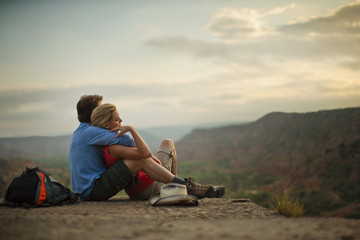 Affectionate young couple take a break from hiking and admire the view while wrapped in each other's arms.